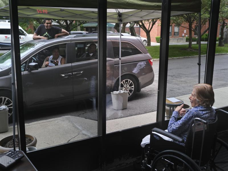 Gloria DeSoto, 92, right, visits with her family, in their car, from a window of the Hebrew Home at Riverdale, in New York, last month.