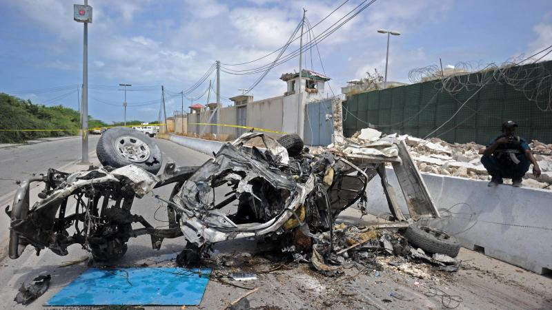 Somali soldiers stand guard next to wreckage from a car bomb outside the U.N.'s office in Mogadishu on Tuesday. At least 13 people were killed in twin bombings near U.N. and African Union buildings adjoining Mogadishu's airport, police said, in what the j
