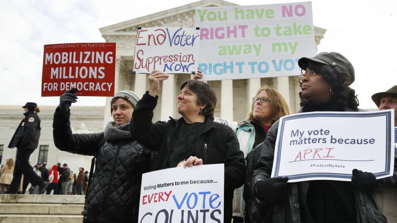 People rally outside of the Supreme Court in opposition to Ohio's voter roll purges in January. The court upheld the controversial law Monday.