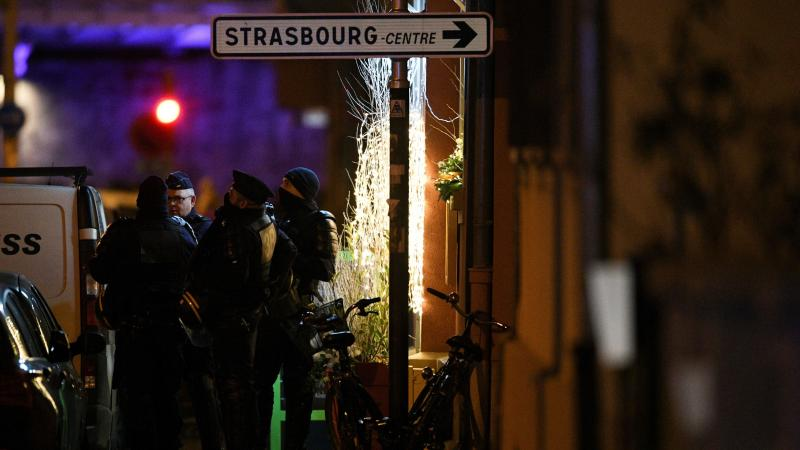 Police officers stand near the place where Cherif Chekatt, the alleged gunman who had been a fugitive since allegedly killing three people at a popular Christmas market in Strasbourg, France, was shot dead by police on Thursday.