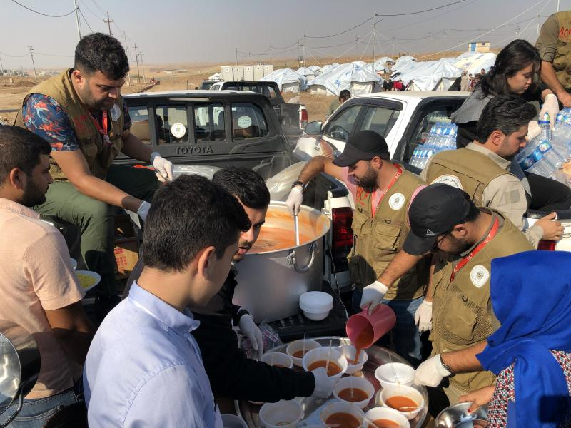 Aid workers dish up rice and stew to refugees at the Gawilan camp in northern Iraq. The camp has accommodated nearly 2,000 new arrivals in the past month.