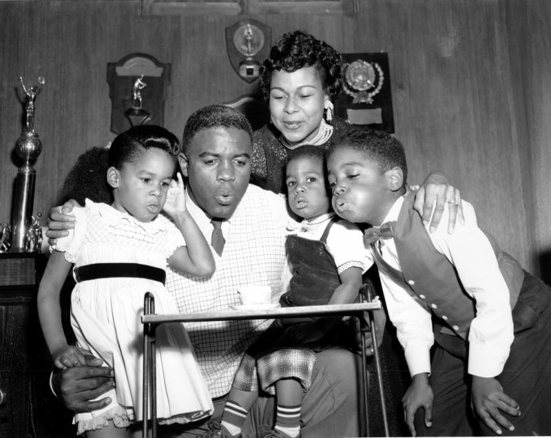 Jackie Robinson draws his family close to help him blow out a birthday candle in 1954. From left, his children Sharon, David, and Jackie Jr., with his wife Rachel, above.