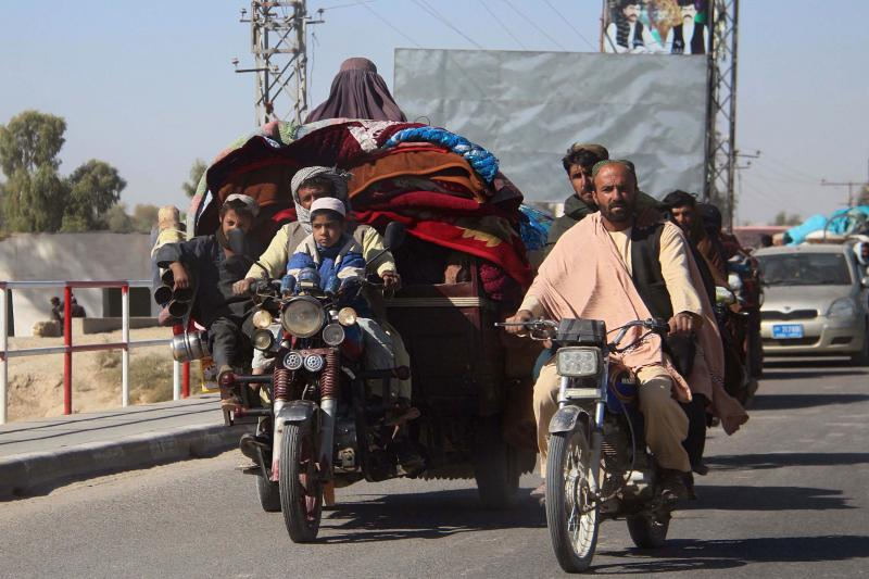 Afghans flee to Lashkar Gah, Helmand's provincial capital, during fighting between Taliban and Afghan security forces on Monday. Local authorities estimate that some 35,000 people have been displaced into Lashkar Gah since a Taliban offensive began in Hel