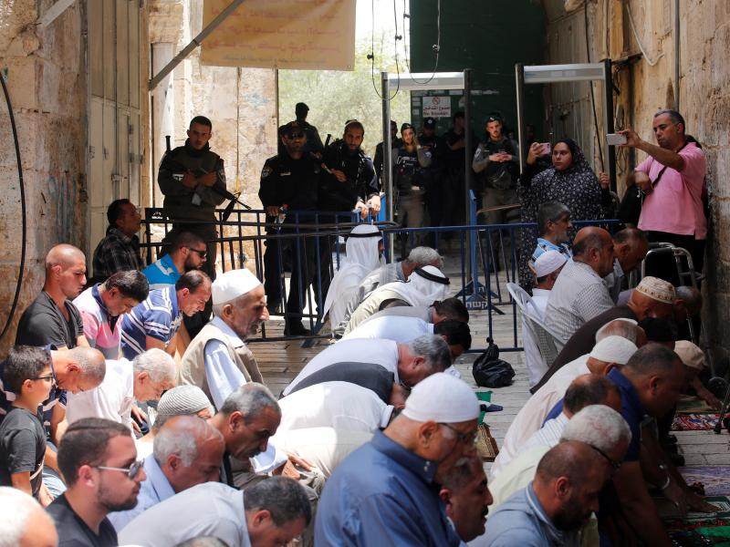 Palestinians pray near new metal detectors that were erected outside one of the main entrances to Al-Aqsa mosque in Jerusalem on Thursday. Increased security measures at the site have touched off protests.