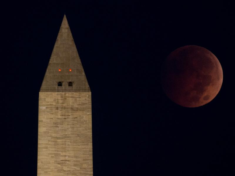 """The """"blood moon"""" eclipse above the Washington Monument just before dawn on the National Mall, in Washington, D.C."""