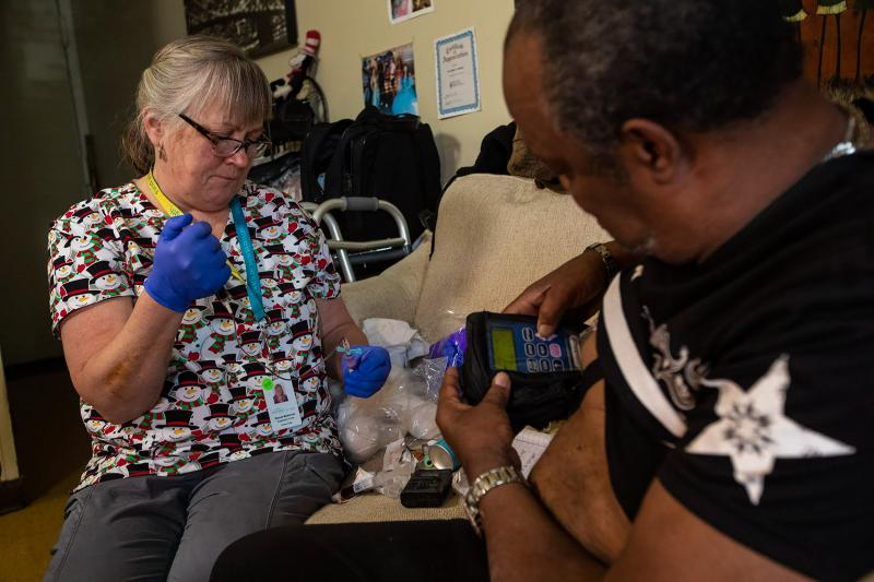 Arthur Jackson (right) gets blood tests during home visits in Boston from nurse Brenda Mastricola. He's also getting intravenous penicillin to treat a serious bone infection in his foot. The medication's pump is connected to an indwelling IV catheter. It'