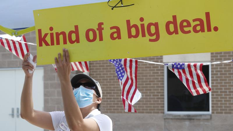 U.S. Census Bureau worker Marisela Gonzales adjusts a sign at a walk-up counting site for the 2020 census in Greenville, Texas, in July.