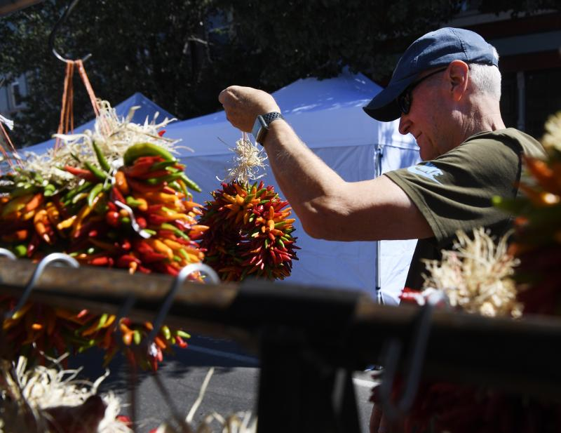 Geoff Walser picks out a ristra, a wreath-like decoration made from dried chiles, to purchase at the annual Pueblo Chile and Frijoles Festival, which draws thousands of chile lovers from Colorado and beyond.