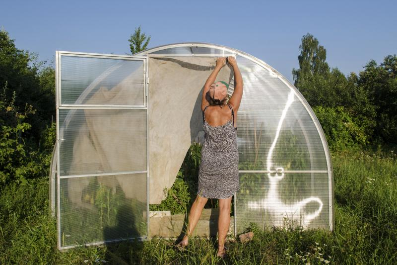 Tatyana Beresneva at her greenhouse, lush with tomatoes. In Soviet times, many dacha owners grew fruits and vegetables because of food shortages. Today, they tend to their gardens as a way to unwind outdoors.