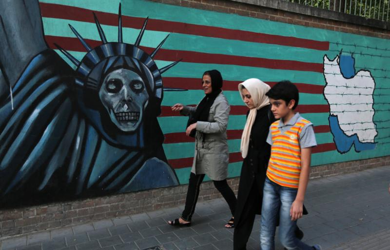 """An Iranian family walks past anti-U.S. graffiti on the wall of the former U.S. embassy in Tehran on Tuesday. President Hassan Rouhani told Iranians that """"all our objectives"""" have been met by a nuclear deal agreed upon Tuesday after talks with six world po"""