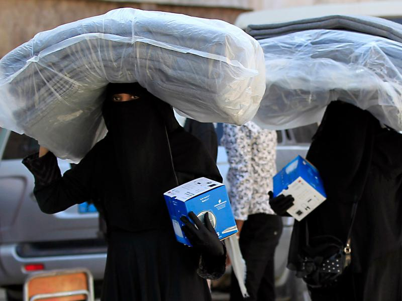 Yemeni women carry blankets and lanterns distributed by the United Nations High Commissioner for Refugees in Sanaa, Yemen.