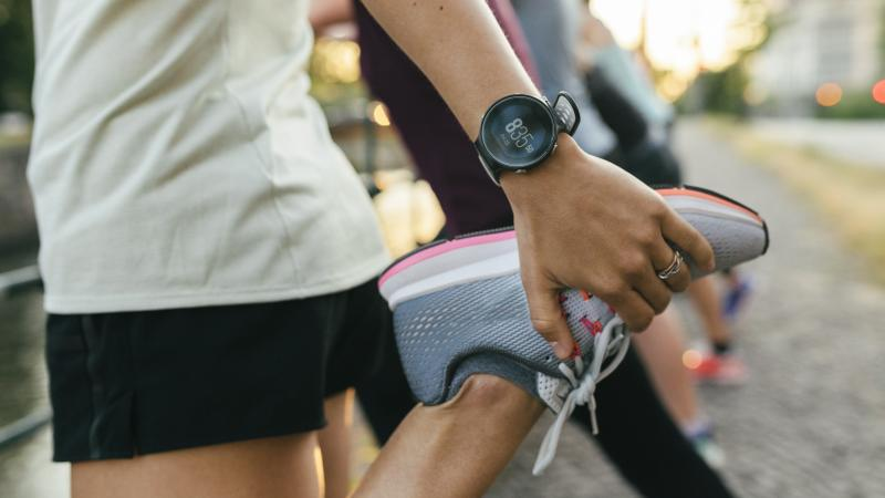 A close up of a woman stretching her legs before going on a run through the city.