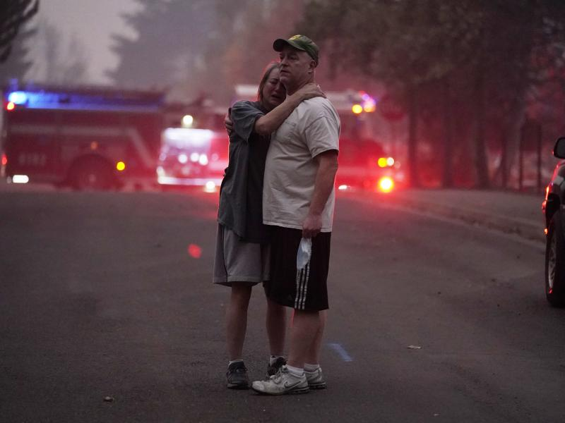 A couple embrace Thursday while touring an area devastated by the Almeda Fire in Phoenix, Ore.