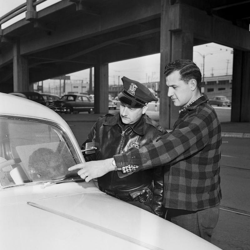 A man shows his pitted windshield to a police officer in Seattle in 1954