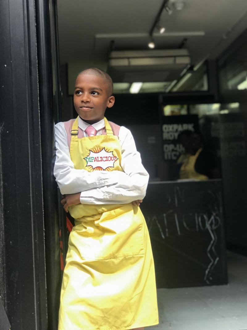 Chef Omari McQueen stands in the doorway of his vegan Caribbean pop-up restaurant Dipalicious.