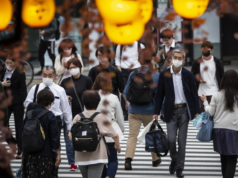 People in Tokyo wear masks on May 7. Daily coronavirus infections in Japan's capital have topped 4,000 — nearly four times as many as a week ago.