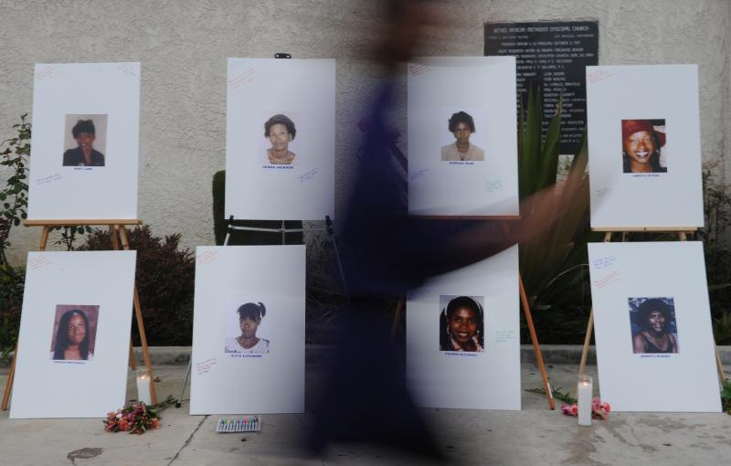 "A woman walks past a memorial for some of the victims who are said to have died at the hands of the serial killer dubbed the ""Grim Sleeper."""