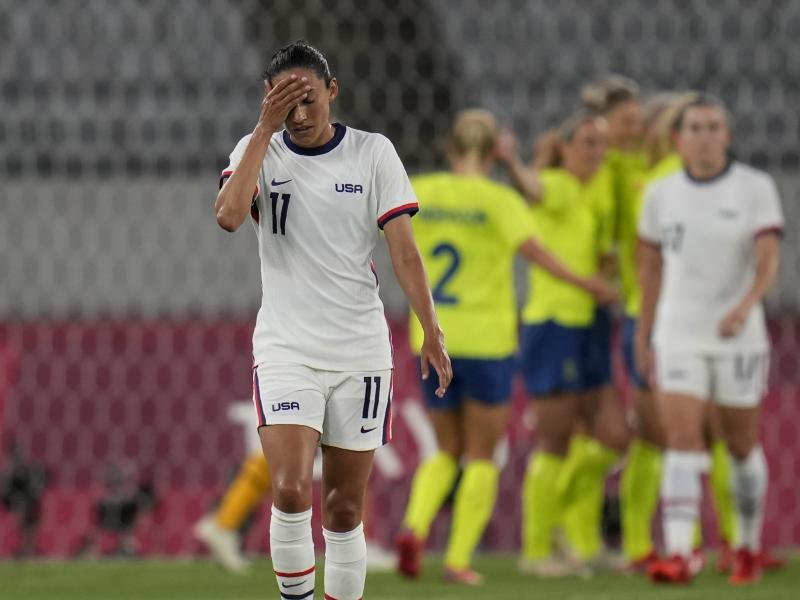 U.S. player Christen Press reacts as Sweden's players celebrate their third goal during a women's soccer match at the Olympics on Wednesday in Tokyo.