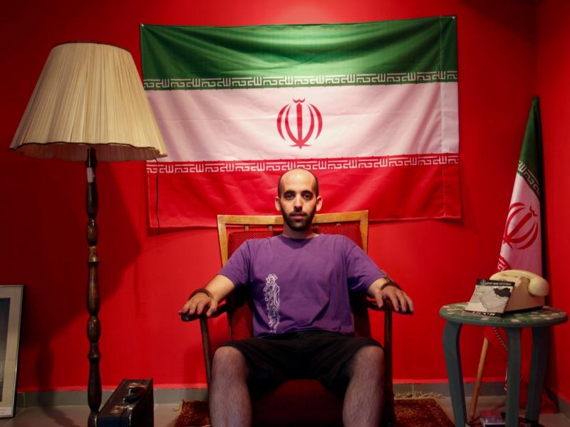 """Israeli artist Matan Pinkas sits in the """"Iranian Embassy in Jerusalem,"""" a cultural project in the works by the Jerusalem art collective Hamabul."""