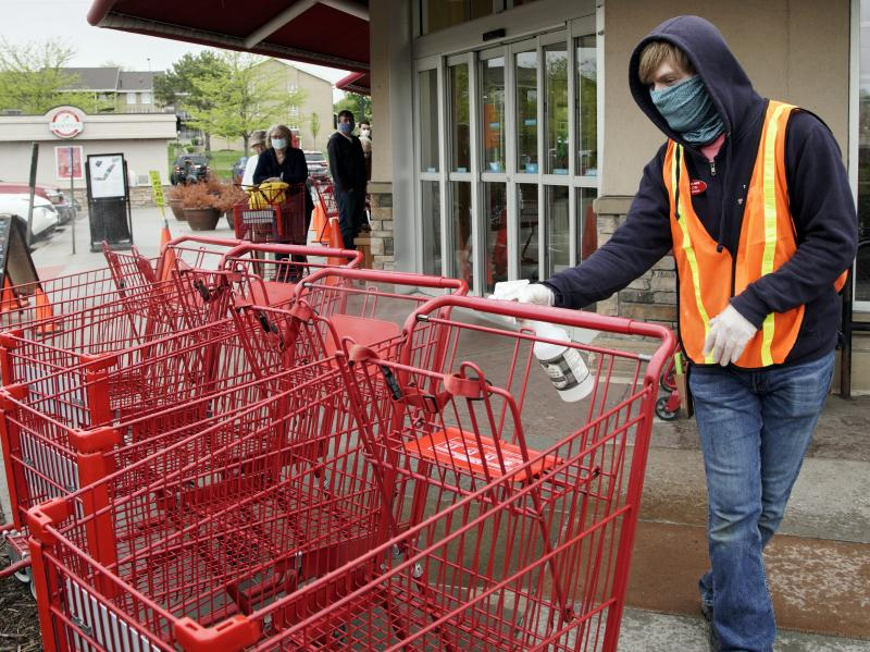 A Trader Joe's worker disinfects shopping carts and controls the number of customers allowed to shop at one time in Omaha, Neb., on May 7, 2020. Grocers like Trader Joe's are offering pay incentives to encourage their workers to get vaccinated against COV