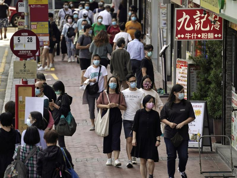 In this Oct. 9, 2020, photo, people walk down a street in Hong Kong. Singapore and Hong Kong have postponed a planned air travel bubble meant to boost tourism amid a spike in coronavirus infections in Hong Kong.