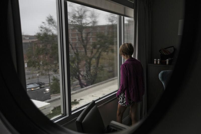 Abbie Hohl watches Hurricane Florence outside a window at Hotel Ballast in Wilmington, N.C., on Friday. The Hohl family lives a half-mile from the hotel but was concerned about flooding from the Cape Fear River.