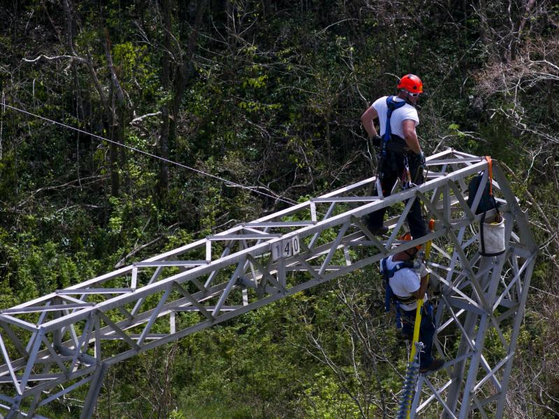Workers restore power lines damaged by Hurricane Maria in Barceloneta, Puerto Rico, in 2017. The Trump administration says it will award nearly $13 billion in infrastructure grants to help the island recover from the storm that hit three years ago.