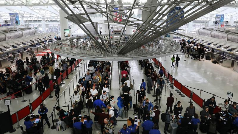 Travelers wait in the security line at John F. Kennedy International Airport in New York. On Wednesday, the Department of Homeland Security warned the state that it was freezing residents' access to Global Entry and similar programs, citing a recent state
