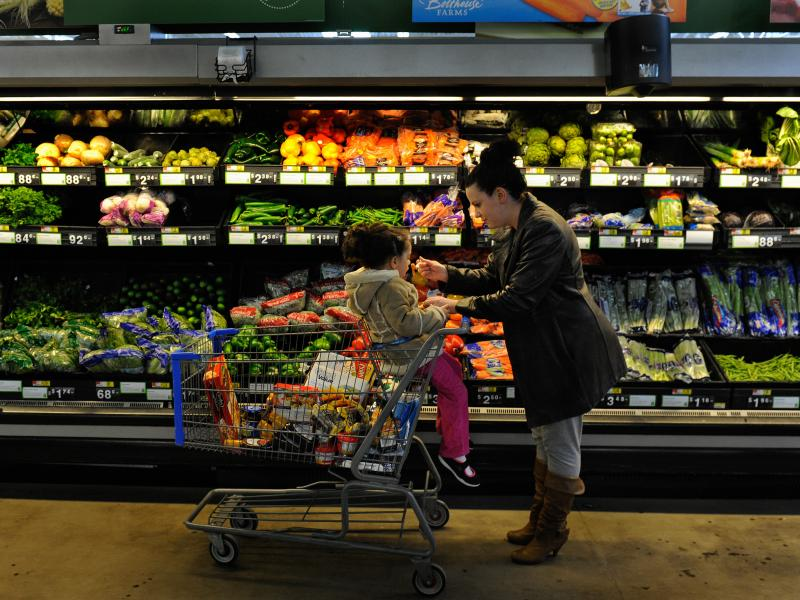 """Rebecka Ortiz offers her daughter a pasta sample at the store where she was using her food stamps to stock up on food for her family in Woonsocket, R.I. The Trump administration is proposing drastic changes in the """"food stamp"""" program, now called SNAP. Pe"""
