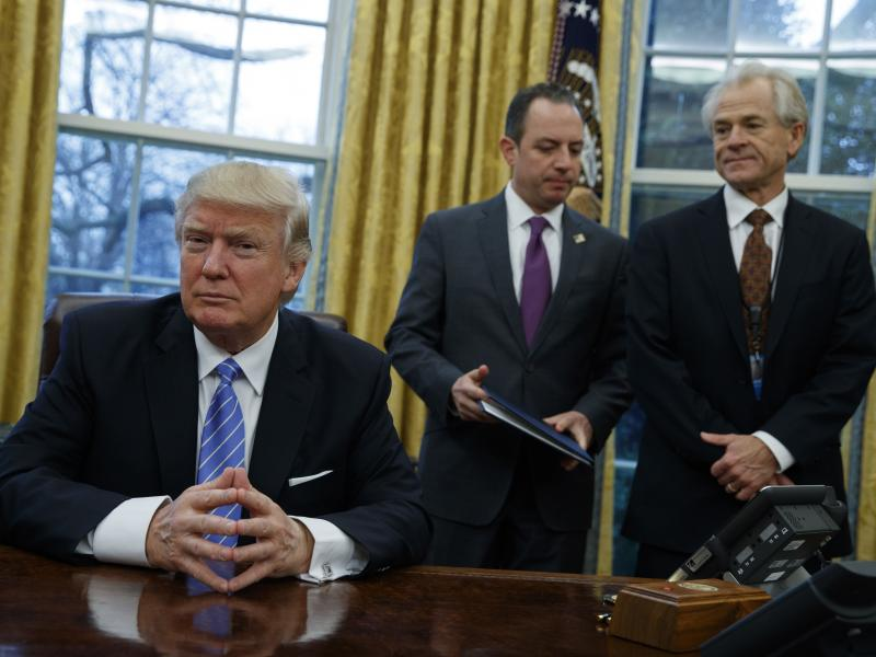 National Trade Council head Peter Navarro (right) and White House Chief of Staff Reince Priebus (center) await President Trump's signing executive orders at the White House on Jan. 23.