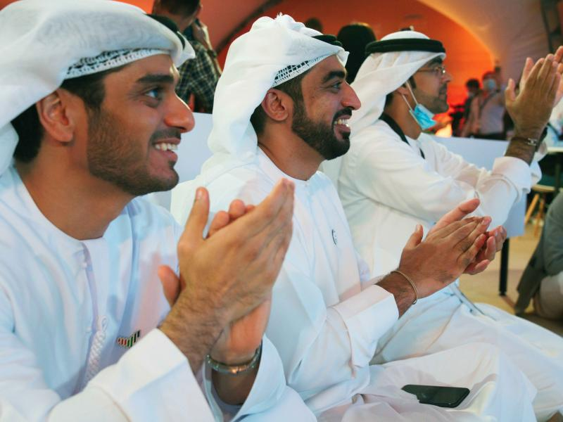 """Emirati men clap as they watch the launch of the """"Amal"""" or """"Hope"""" space probe at the Mohammed bin Rashid Space Center in Dubai, United Arab Emirates, on Monday. The probe, the country's first interplanetary spacecraft, was launched from Japan."""