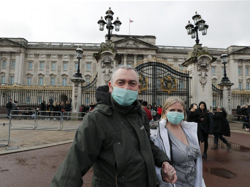 A couple wear face masks as they visit Buckingham Palace in London on Saturday. After criticism for responding slowly, the United Kingdom has urged the public to avoid unnecessary contact.