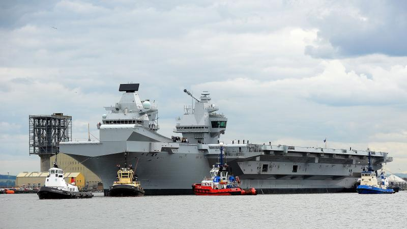 The HMS Queen Elizabeth, one of two brand-new British aircraft carriers, trails a collection of tug boats on the Firth of Forth in Scotland last month. U.K. Foreign Secretary Boris Johnson says the massive carriers, which have been billed as some of the b