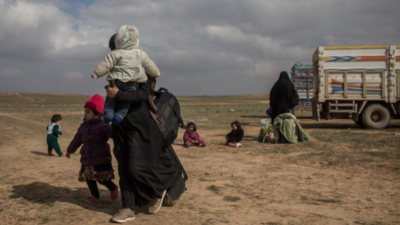 Civilians who have fled fighting in Bagouz wait to board trucks after being screened by members of the Syrian Democratic Forces (SDF) at a makeshift screening point in the desert on Saturday in Bagouz, Syria. After weeks of fighting the SDF announced the