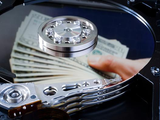 Dollar bills are reflected in a computer hard drive.