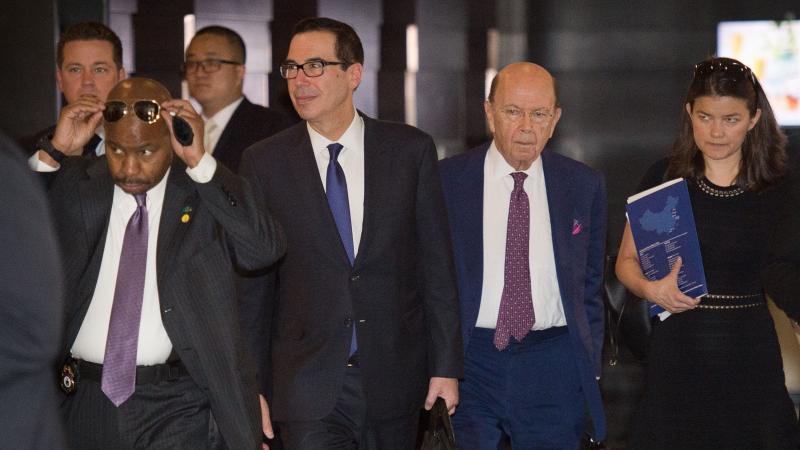 """Treasury Secretary Steven Mnuchin (center left) and Commerce Secretary Wilbur Ross (center right) walk through a hotel lobby as they head to a state guest house to meet Chinese officials in Beijing on Friday. The talks included a """"thorough exchange of vie"""
