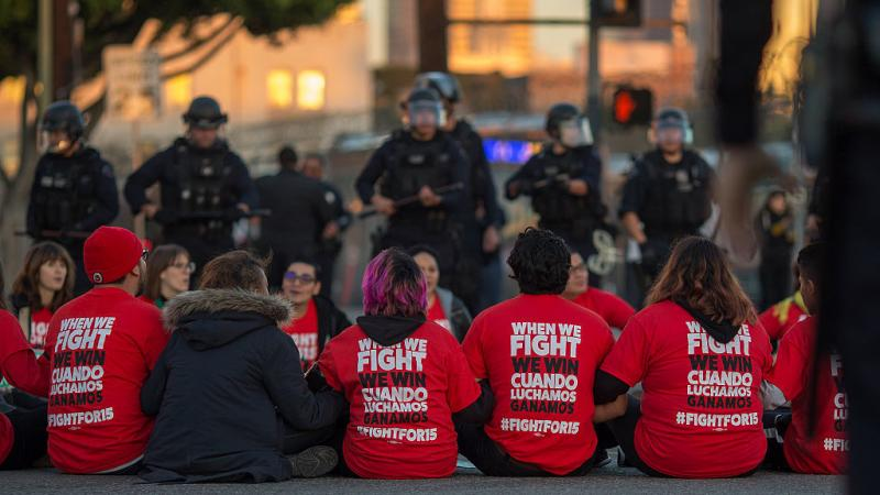 """Police surround McDonald's restaurant employees who were sitting in an intersection in Los Angeles after walking off the job to demand a $15 minimum wage and union rights during nationwide """"Fight for $15"""" protests on Tuesday."""