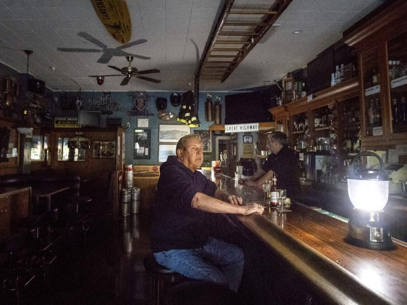Joseph Pokorski drinks a beer at The Town Square as downtown Sonoma, Calif., remains without power on Wednesday.