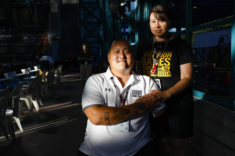 Retired Staff Sgt. Matt Lammers holds the hand of his wife, Alicia, before the swimming competition at the 2019 Department of Defense Warrior Games in Clearwater, Fla. Alicia has been Matt's official caregiver for nearly eight years, but she was cut from