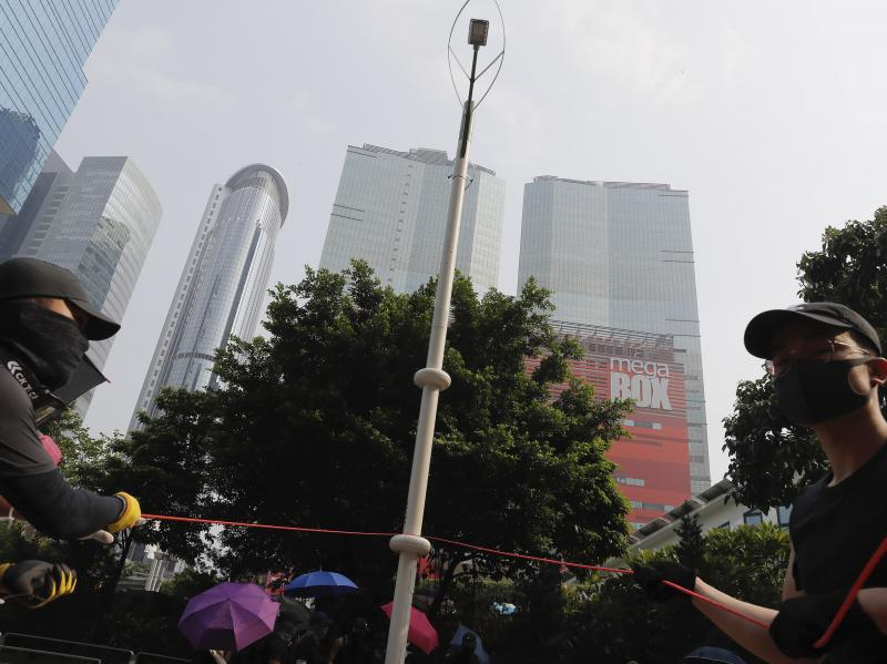 Demonstrators try to pull down a smart lamppost during the protest in Hong Kong on Saturday that turned violent. The smart lampposts are raising fears of stepped-up surveillance from authorities.