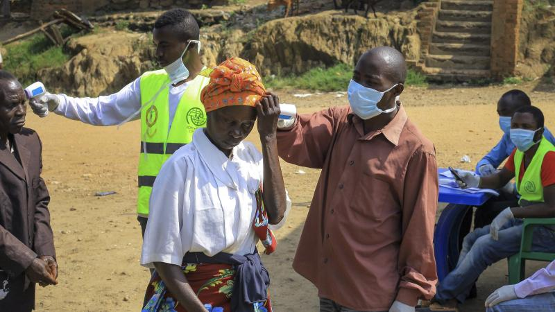 People crossing the border have their temperature taken to check for symptoms of Ebola, near Kasindi, eastern Congo, on Wednesday.