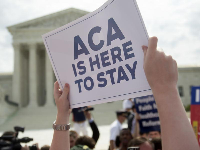 A demonstrator celebrated outside the U.S. Supreme Court in 2015 after the court voted to uphold key tax subsidies that are part of the Affordable Care Act. But federal taxes and other measures designed to pay for the health care the ACA provides have not