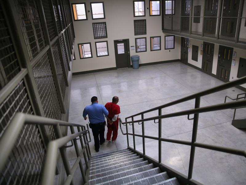 """A guard escorts a detained immigrant from his """"segregation cell"""" back into the general population at the Adelanto Detention Facility in November 2013. Today the privately run ICE facility in Adelanto, Calif., houses nearly 2,000 men and women and has come"""