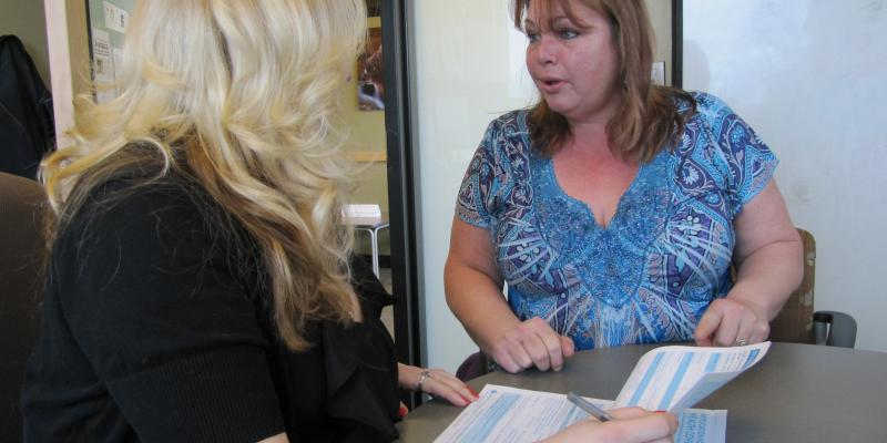 Cheryl Stumph goes over paperwork with a medical worker. She finally has health insurance to take care of her family's medical needs.