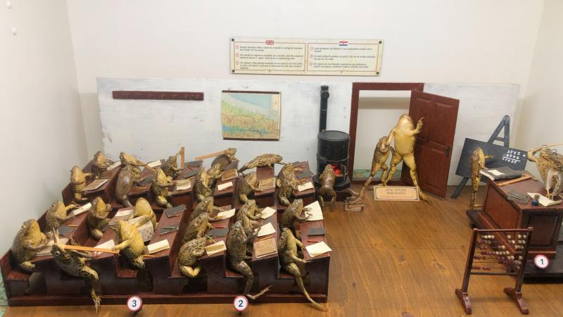 A Froggyland diorama shows a teacher trying to control a class in which students are hitting each other with rulers, arriving late to class and balancing pencils on their noses. Each  diorama displays anthropomorphized frogs in human scenes of the early 2