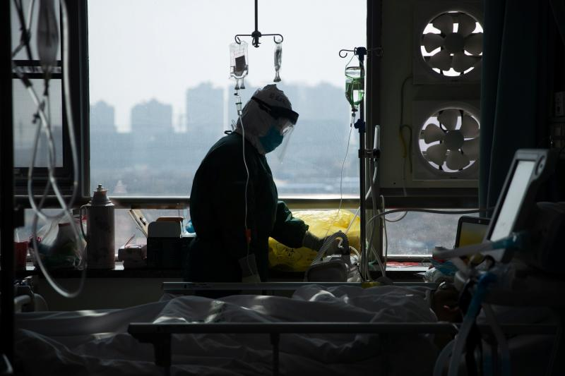 A medical worker in a protective suit tends to a patient in a hospital in Wuhan, China.
