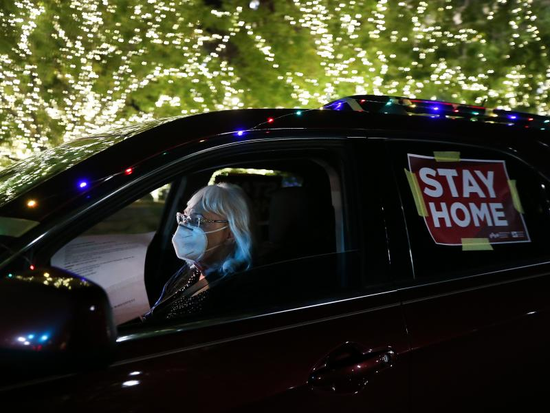 """A """"Stay Home"""" sign is taped to a driver's vehicle as she passes Christmas lights during a car caravan of nurses calling for people to remain home amid a coronavirus surge last month in El Paso, Texas."""
