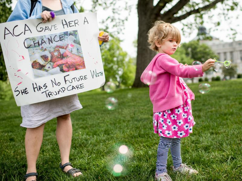 Charlie Wood of Charlottesville, Va., plays with bubbles during a May 4, 2017, rally near the Capitol to oppose proposed changes to the Affordable Care Act. Charlie was born a few months prematurely, and her mother, Rebecca (left), fears changes to the he