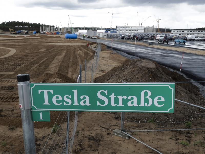 "A street sign says ""Tesla Street 1"" in front of the construction site of the Tesla Gigafactory near Berlin. The electric automaker plans to start building cars this summer at its first European production site."
