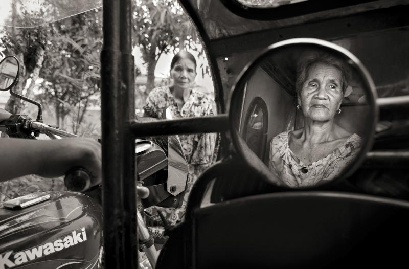 """Isabelita Vinuya, 88, reflected in mirror, bids farewell to Perla Bulaon Balingit in the village of Mapaniqui in Pampanga. They are two of the last living """"comfort women"""" of the Philippines. On Nov. 23, 1944, Vinuya, Balingit and some 100 other girls and"""